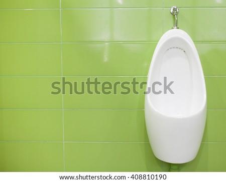 Modern white ceramic urinals in men's bathroom on green tiles background - stock photo