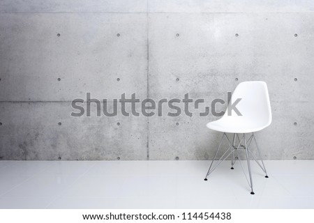 modern white chair and concrete wall - stock photo
