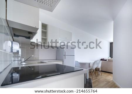 Modern, white compact kitchen interior design in small apartment - stock photo