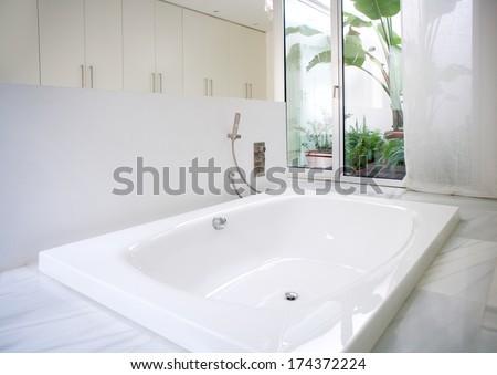 Modern white house bathroom bathtub with marble floor and courtyard skylight - stock photo
