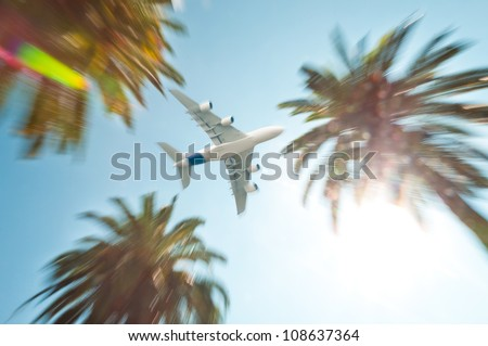 Modern white jet air plane in sky above palm trees at tropical resort. Sun with lens flare. - stock photo