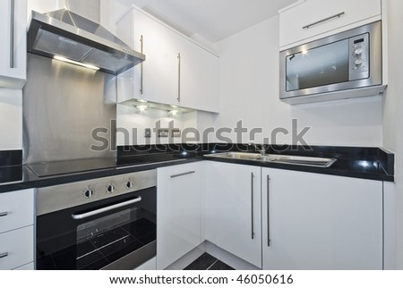 modern white kitchen unit with built-in electric appliances - stock photo