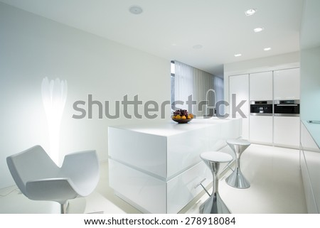 Modern white kitchen with extravagant dining space - stock photo