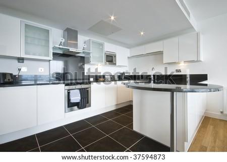 modern white kitchen with granite work top dark tiled floor and appliances - stock photo