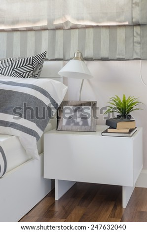 modern white lamp and plant on white table in bedroom at home