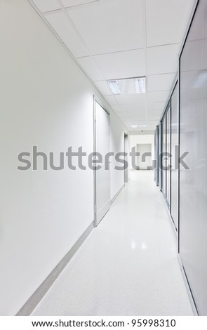 Modern white long corridor with glass doors on one side - stock photo