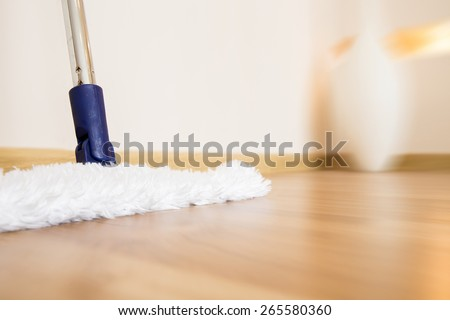 Modern white mop cleaning wooden floor from dust, motion blur - stock photo