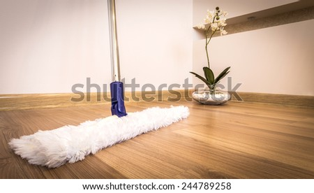 Modern white mop cleaning wooden floor in house - stock photo