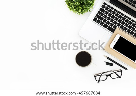 Modern White Office Desk Table With Laptop Computer, Smartphone With Black  Screen Over A Notebook