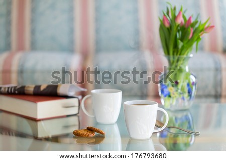 Modern white porcelain cup of black coffee on glass table with spoon and ginger biscuits. Book newspaper and vase of tulips in the background out of focus - stock photo