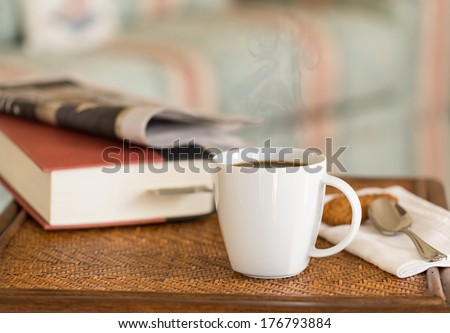 Modern white porcelain cup of black coffee on wooden wicker table with spoon and ginger biscuits and book - stock photo
