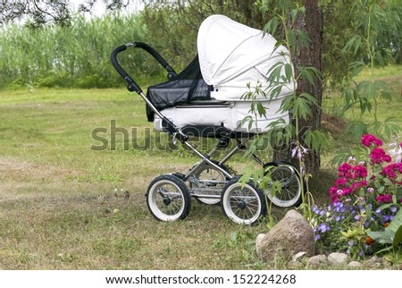 Modern white pram with supposedly sleeping baby under the tree in natural environment  - stock photo