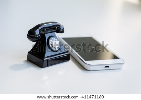 Modern white smartphone and toy retro telephone standing together on a white background as a symbol of technological evolution
