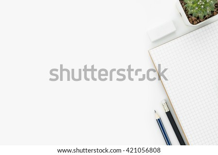 Modern white working table with notebook, pencils and eraser. Top view with copy space. - stock photo