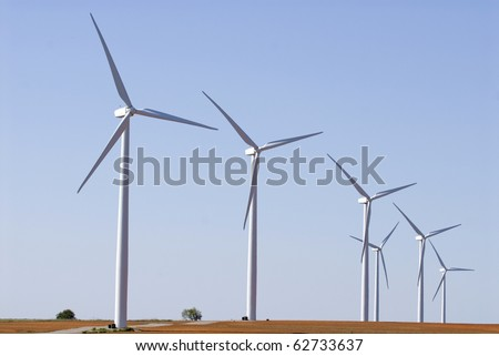 Modern wind farm located on farmland in Midwest America - stock photo