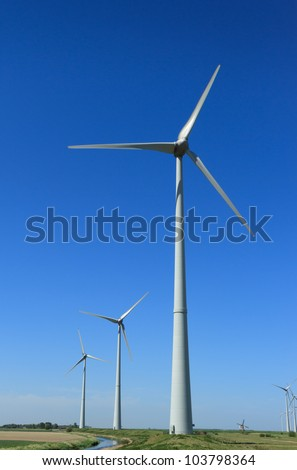 Modern wind turbines in the countryside, and an traditional one in the background.