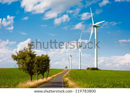 Modern wind turbines over green fields and a road - stock photo