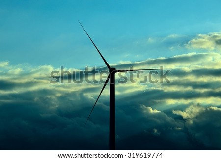 Modern windmill backlit at dawn with low clouds background and blue sky - stock photo