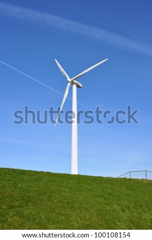 Modern windmill in the water behind a green grassy dike - stock photo