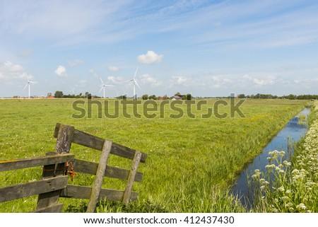 Modern windmills at the horizon in province Friesland near Idsegahuizum. - stock photo