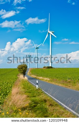 Modern windmills by a rural road through green fields - stock photo