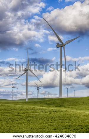 Modern windmills create clean energy using wind power on the wheat and grain farms in the Palouse area of Eastern Washington State in the USA.