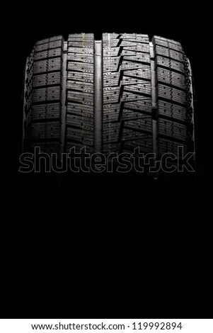 Modern winter performance tire. Isolated on a black background. Vertical composition. - stock photo