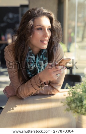 Modern woman. Beautiful young woman texting a message on a mobile phone. - stock photo