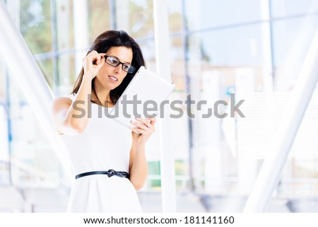 Modern woman reading digital business info in tablet. Young businesswoman using touch pad.
