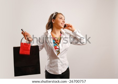 Modern woman wearing white jacket talking on the phone and holding shopping bags - stock photo