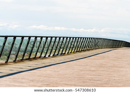 Modern wooden bridge with glass railings