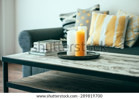 Modern wooden coffee table and cozy sofa with pillows. Living room interior and home decor concept. Toned image - stock photo