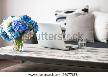 Modern wooden coffee table, laptop and cozy sofa with pillows. Living room interior and home decor concept - stock photo