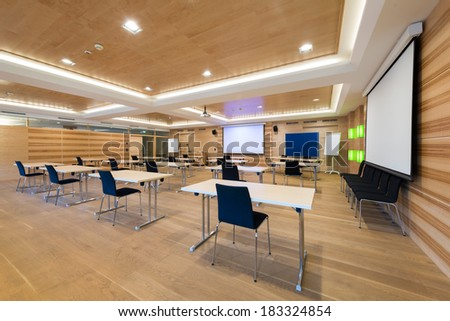 modern wooden conference room with tables an chairs and projector screen - stock photo