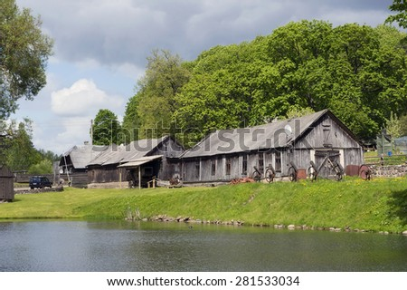 Modern wooden European village on lake bank spring landscape - stock photo