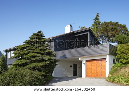 Modern wooden house with garage in Norway, summer day - stock photo