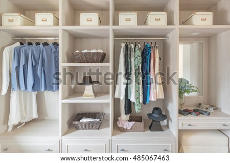 Modern Wooden Wardrobe With Clothes Hanging On Rail In Walk Closet Design Interior