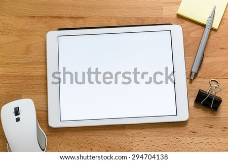 Modern working desk with digital tablet presenting a blank screen for advertising - stock photo