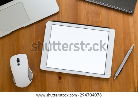 Modern working desk with tablet showing a blank screen for advertising - stock photo