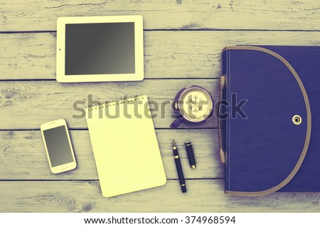 Modern workplace with digital tablet, mobile phone, pen, cup of tea and papers with numbers. - stock photo