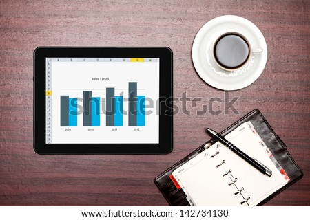 Modern workplace with digital tablet showing charts and diagram on screen - stock photo