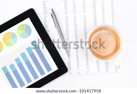 Modern workplace with digital tablet showing charts and diagram on screen, cup of coffee, pen and paper with numbers. - stock photo