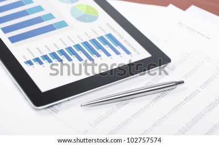 Modern workplace with digital tablet showing charts and diagram on screen, pen and paper with numbers. - stock photo