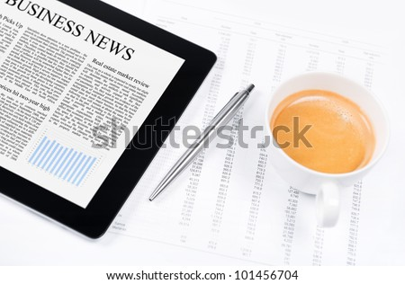 Modern workplace with digital tablet showing charts and diagram on screen, pen, cup of coffee and paper with numbers. - stock photo