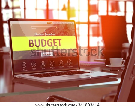 Modern Workplace with Laptop showing Landing Page with Budget Concept. Toned Image with Selective Focus. - stock photo