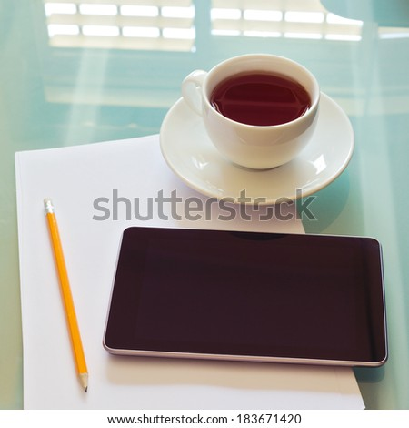 Modern workplace with tablet device, pencil, cup of tea and papers - stock photo