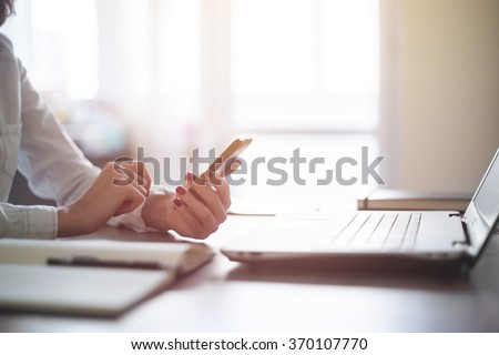 Modern workplace woman using mobile phone in office. - stock photo