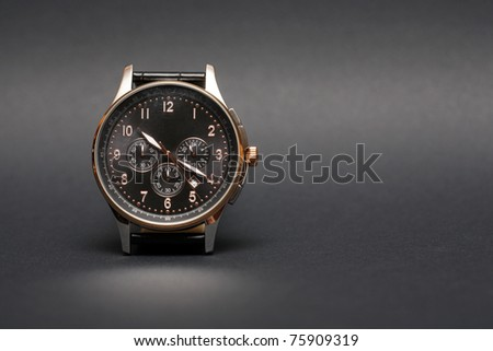 Modern wristwatch standing on nice dark background with copy space - stock photo
