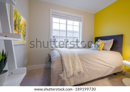 Modern yellow bedroom interior in a luxury house with reclaimed wood bedside tables - stock photo