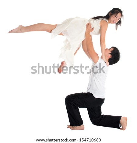 Modern young Asian teens couple contemporary dancers dancing in front of the studio background, full length isolated white. - stock photo
